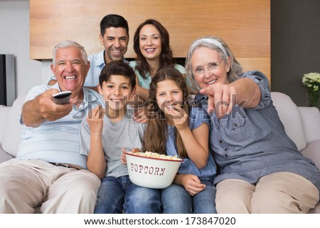 Portrait of happy extended family watching tv on sofa in the living room at home - stock photo