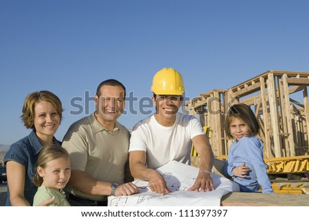Portrait of happy family and male architect with blueprint at construction site