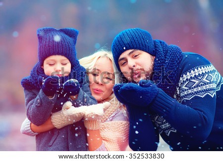 portrait of happy family blowing winter snow outdoors - stock photo