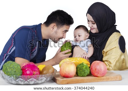 Portrait of happy family cooking salad for dinner,  isolated on white background