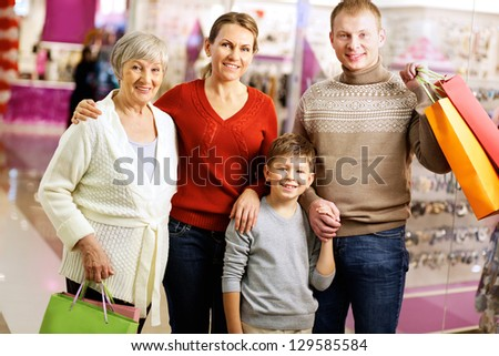 Portrait of happy family during shopping in the mall looking at camera