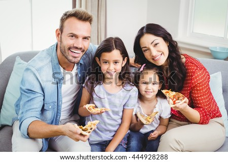 Portrait of happy family eating pizza while sitting on sofa at home - stock photo