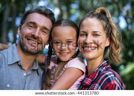 Portrait of happy family embracing in back yard - stock photo