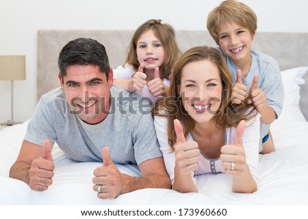 Portrait of happy family gesturing thumbs up in bed - stock photo