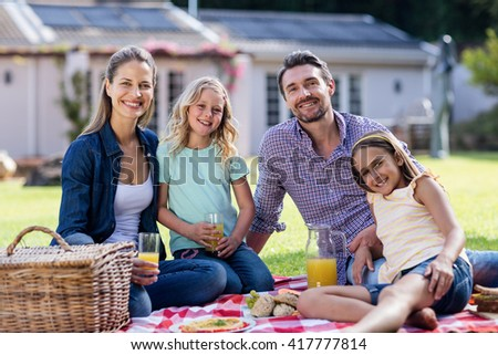 Portrait of happy family having a picnic in the garden - stock photo