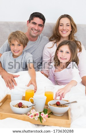 Portrait of happy family having breakfast in bed