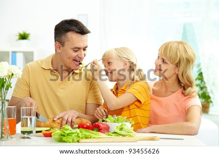 Portrait of happy family having breakfast in the morning in the kitchen - stock photo