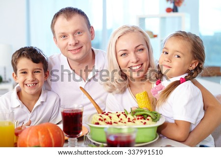 Portrait of happy family having dinner at home - stock photo