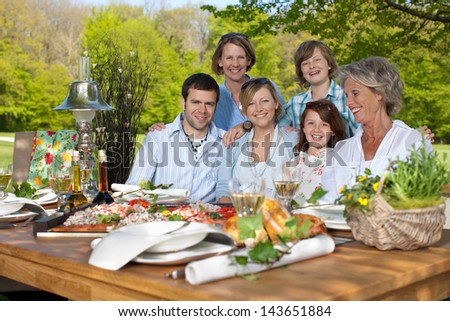 Portrait of happy family having picnic in the garden - stock photo