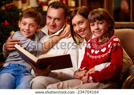 Portrait of happy family having rest on Christmas evening - stock photo