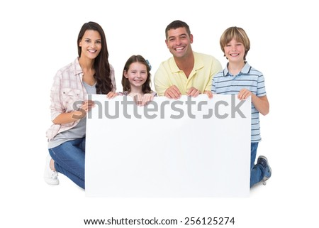Portrait of happy family holding billboard over white background