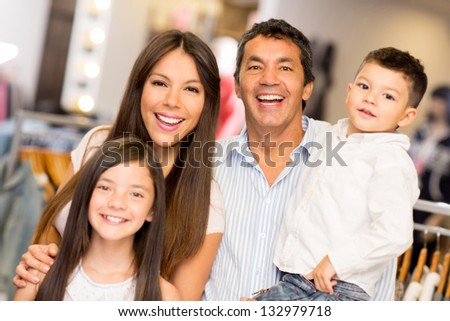 Portrait of happy family in a clothing store smiling - stock photo