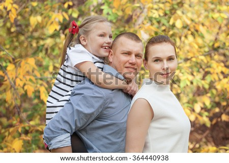 Portrait of happy family in fall park, outdoor - stock photo