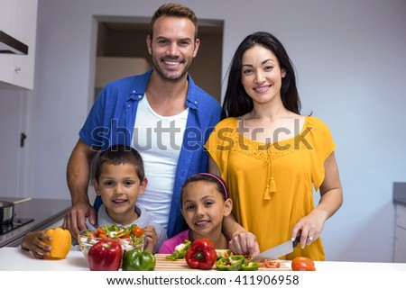 Portrait of happy family in the kitchen chopping vegetables at home - stock photo