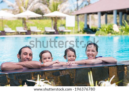 Portrait of happy family in the pool - stock photo