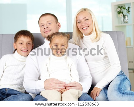 Portrait of happy family in white pullovers looking at camera