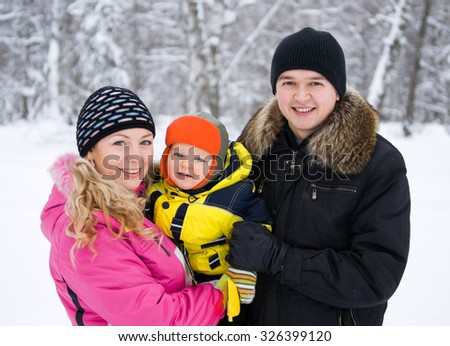 Portrait of happy family in winter forest - stock photo