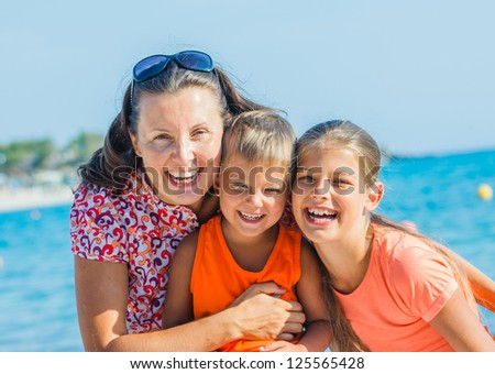 Portrait of happy family laughing and looking at camera on the beach - stock photo