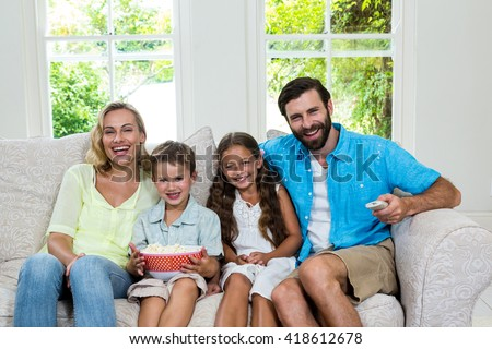 Portrait of happy family laughing while watching tv at home - stock photo