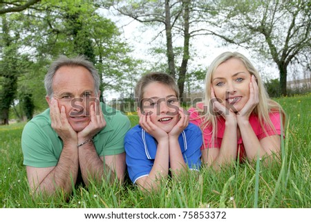 Portrait of happy family laying in grass - stock photo
