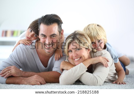 Portrait of happy family laying on carpet - stock photo