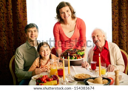 Portrait of happy family looking at camera on holiday evening  - stock photo