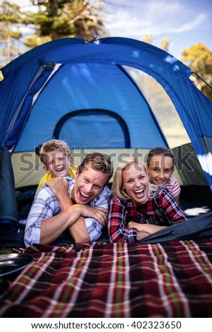 Portrait of happy family lying in a tent - stock photo