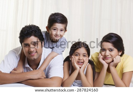 Portrait of happy family lying in bed - stock photo