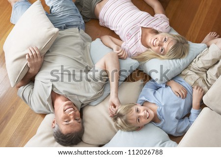 Portrait of happy family lying on floor