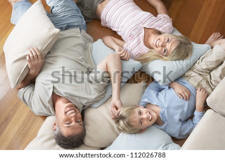 Portrait of happy family lying on floor - stock photo