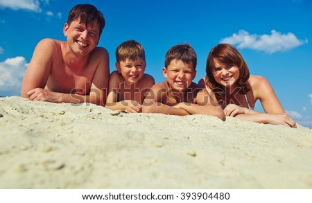 Portrait of happy family lying on sand and taking a tan - stock photo