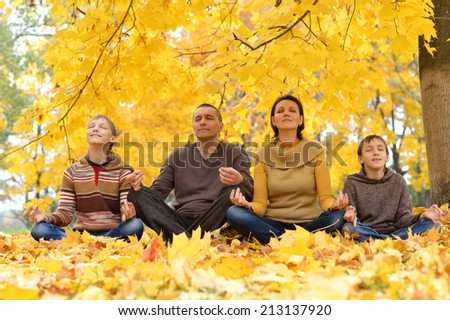 Portrait of  happy family meditate in autumn park - stock photo