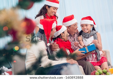 Portrait of happy family members in Santa caps sitting at home on Christmas eve - stock photo