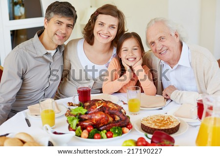 Portrait of happy family members sitting at festive table on Thanksgiving day and looking at camera