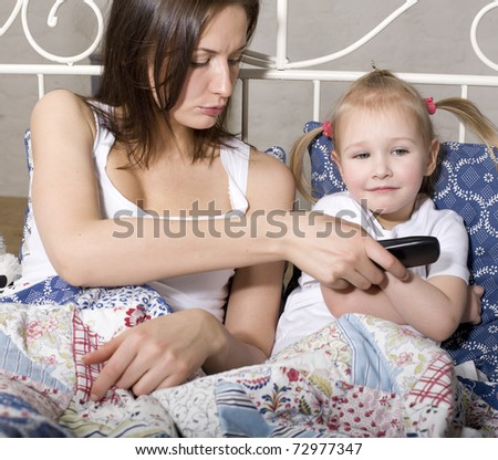portrait of happy family, mother and daughter in bed watching television
