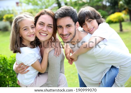 Portrait of happy family of four - stock photo