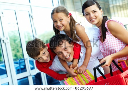 Portrait of happy family of four having fun after shopping
