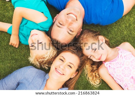 Portrait of Happy Family of Four Outside On the Grass - stock photo