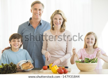 Portrait of happy family of four preparing food together at counter in kitchen