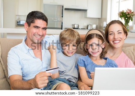 Portrait of happy family of four shopping online in house