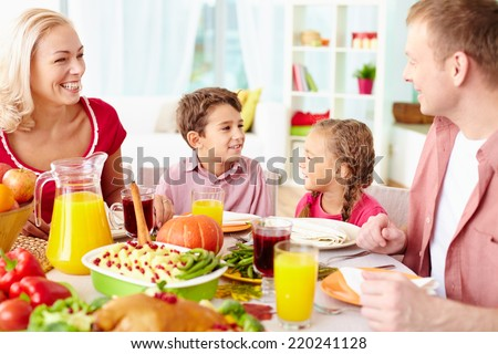 Portrait of happy family of four sitting at festive table and communicating