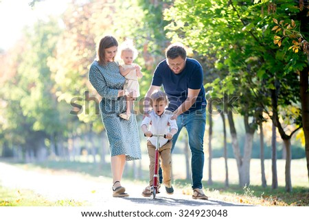Portrait of happy family of four walking together in park in autumn. Young beautiful mother holding cute toddler daughter wearing dress, father teaching son to ride kick scooter, full length - stock photo