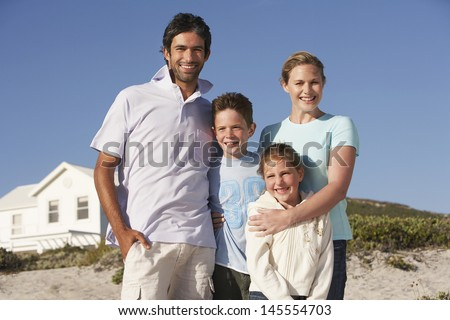 Portrait of happy family of four with beach house in background