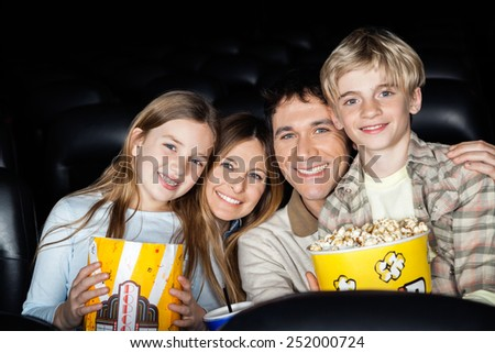 Portrait of happy family of four with popcorn at cinema theater - stock photo