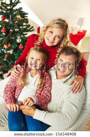 Portrait of happy family of three looking at camera on Christmas day