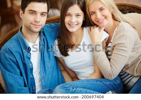 Portrait of happy family of three looking at camera with smiles - stock photo