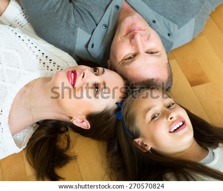 Portrait of happy family of three on the floor at home. Focus on woman