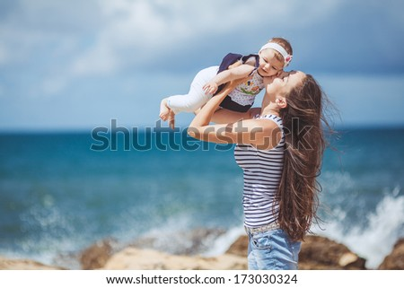 portrait of Happy Family of two mother and child having fun by the Sea shore - stock photo