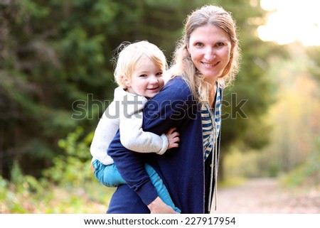 Portrait of happy family of two, young active mother and her blonde funny toddler daughter enjoying sunny day in the forest - stock photo