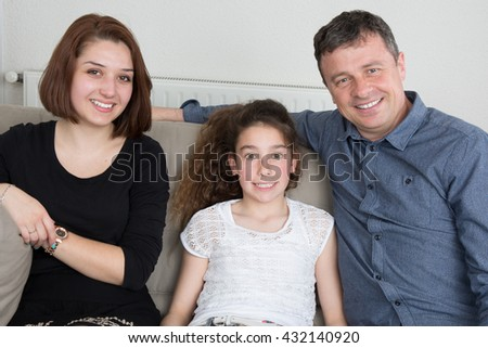 Portrait of happy family on sofa at home